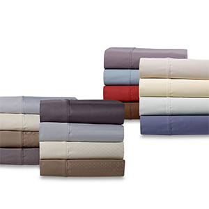 Four piles of a variety of colors of bed sheets photo