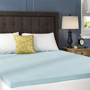Light blue foam mattress topper on top of a bed with pillows photo