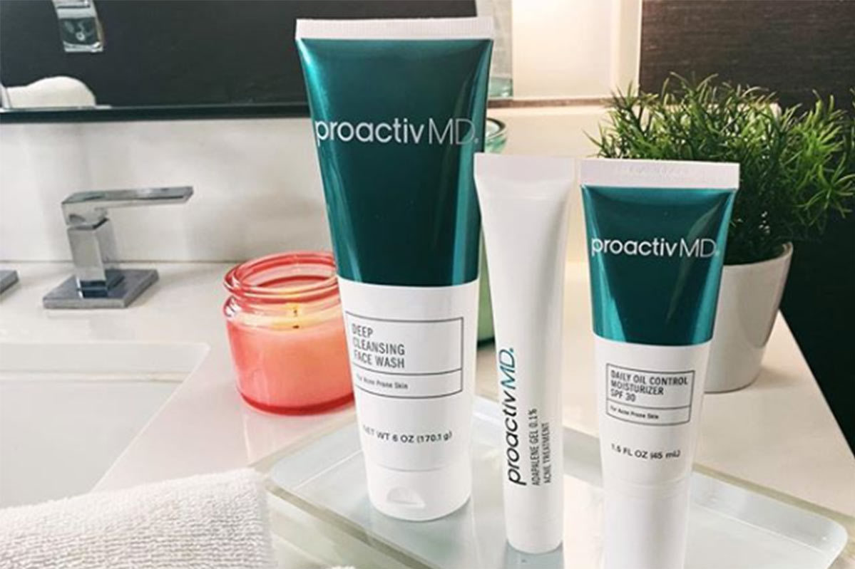 Three tubes of ProactivMD from the Ready, Set, Glow kit sit on a bathroom counter in front of a sink photo