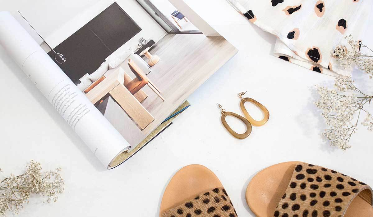 Leopard sandals next to tan earrings, and a printed blouse
