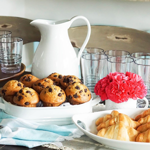 A brunch spread featuring a large white pitcher, muffins, crossiants, and serveral drink glasses photo