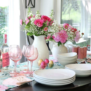 A dining table with pink flowers in white vases, pink wine glasses, and crisp white dinnerware. photo