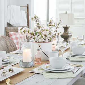 Wooden dining table with cherry blosoms ans candles as the centerpiece and white dinnerware photo