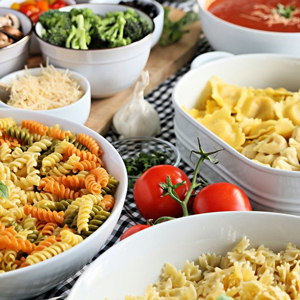 A closeup of a variety of pasta dishes in large white serving bowls photo