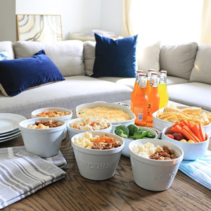 Coffee table with several white popcorn dishes filled with a variety of snacks photo