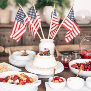 Wooden dining table with an American flag centerpiece surrounded by a variety of patriotic themed desserts photo