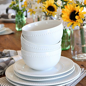 A stack of white bowls on a stack of white plates with a sunflower centerpiece in the background photo