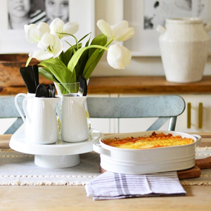 Dining table with a serving dish of lasagna and a cake stand with small pitchers on top as a centerpiece photo