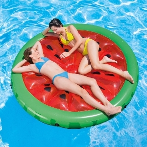 Two women lounge on a large watermelon-shaped pool float photo
