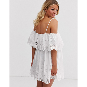 A pregnant woman wears a white eyelet off-the-shoulder dress photo