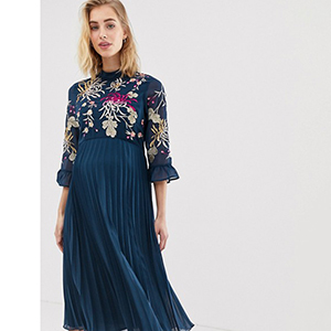 A pregnant woman wears a navy embroidered pleated midi dress photo
