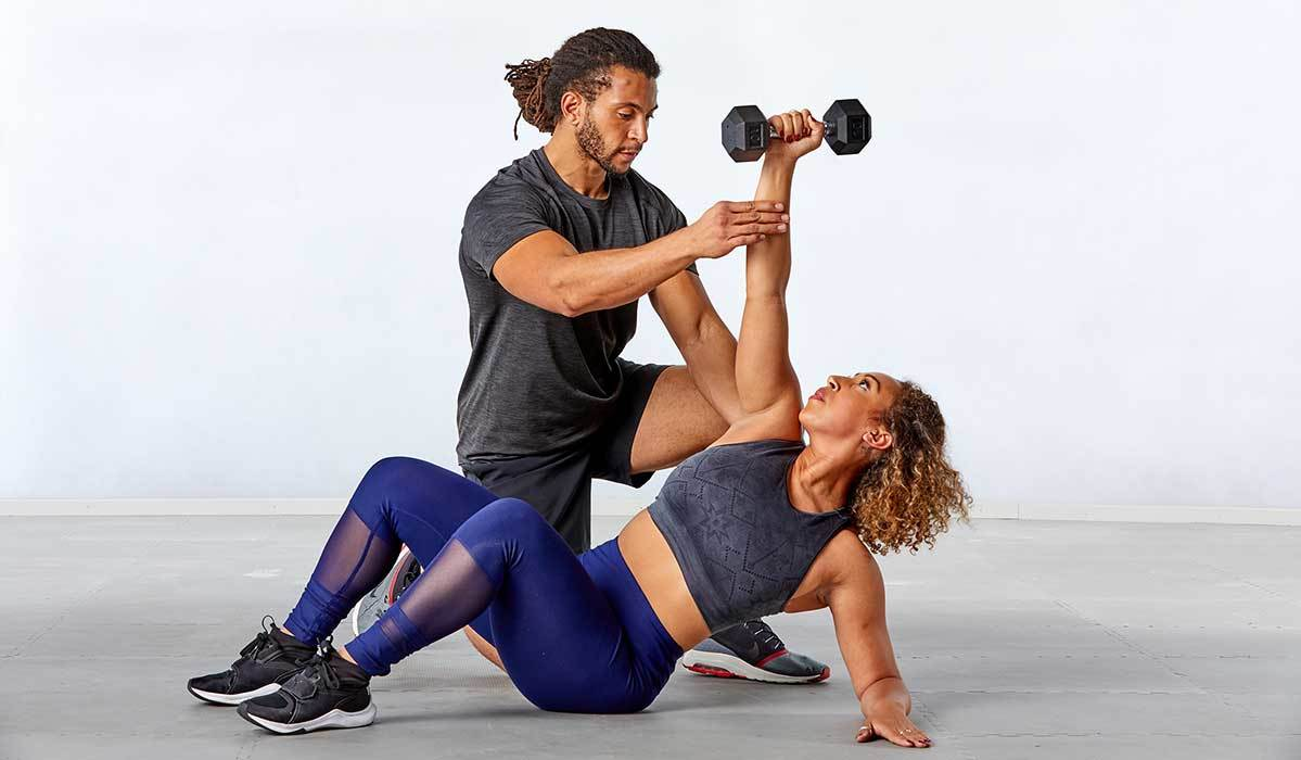 Trainer Devin Wiggins helping a woman with her form during a 600 Secs workout photo