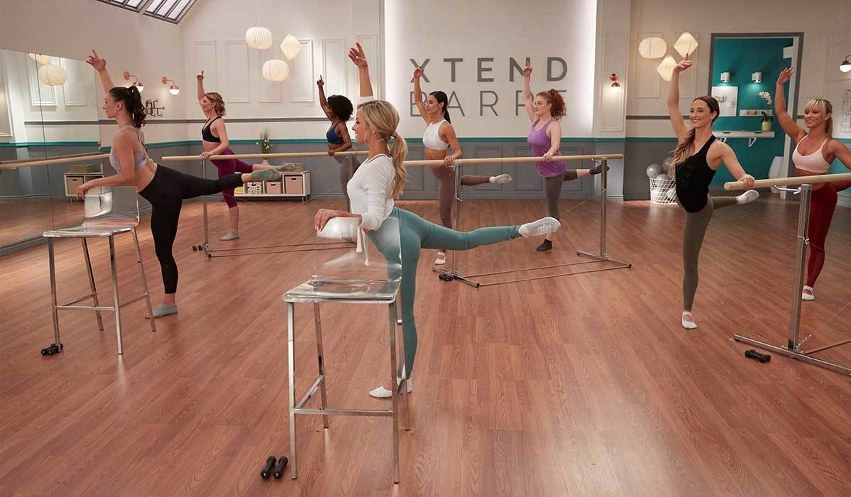 A large group of women performing in a barre workout class photo