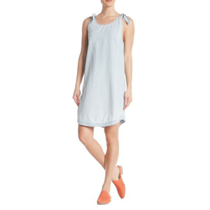 Woman wearing a light wash cotton dress with tie shoulder straps and peach mules. photo