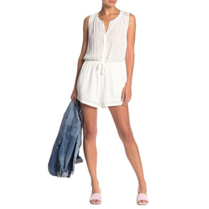 Woman wearing a white front button romper with a tie waist holding a jean jacket. photo
