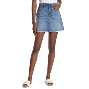 Woman wearing a medium wash jean skirt and white sandals. photo
