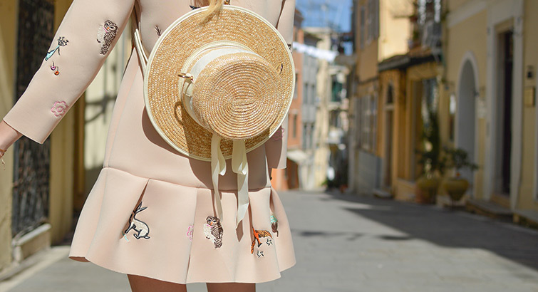 Woman walking on a street in a dress and hat.