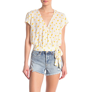 Woman wearing a white patterned wrap top with jean shorts. photo