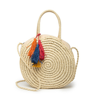 Circle straw tote with colorful tassels on the handle. photo