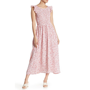 Woman wearing a dot print maxi dress with white wedge sandals. photo