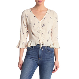 Woman wearing a white patterned peplum top and jeans. photo