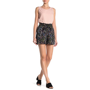 Woman wearing black patterned tie front shorts with light pink tank and black heels. photo