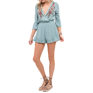 Woman wearing a light blue embroidered romper with gladiator sandals. photo