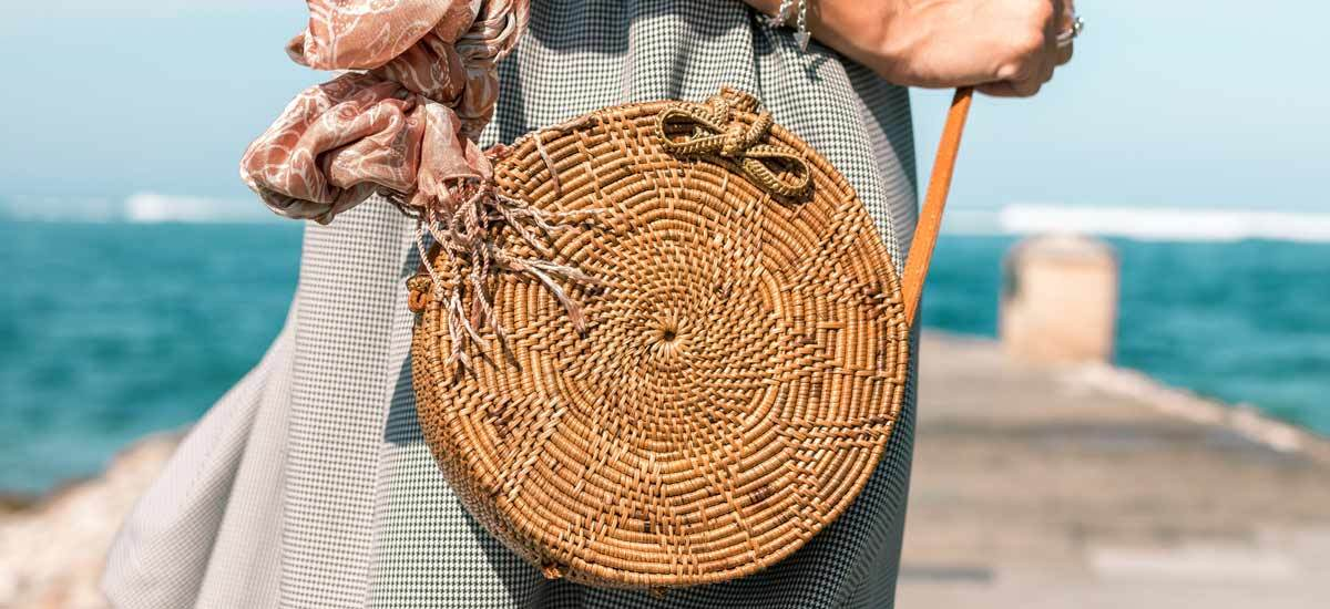 A woman carrying a straw circle bag