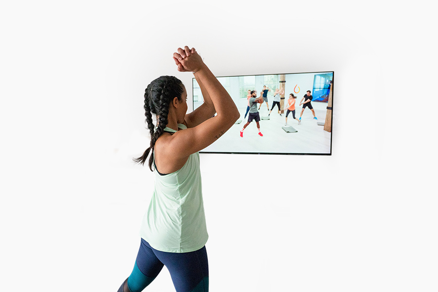 Woman wearing active clothes while working out with the Daily Burn app on her TV screen. photo