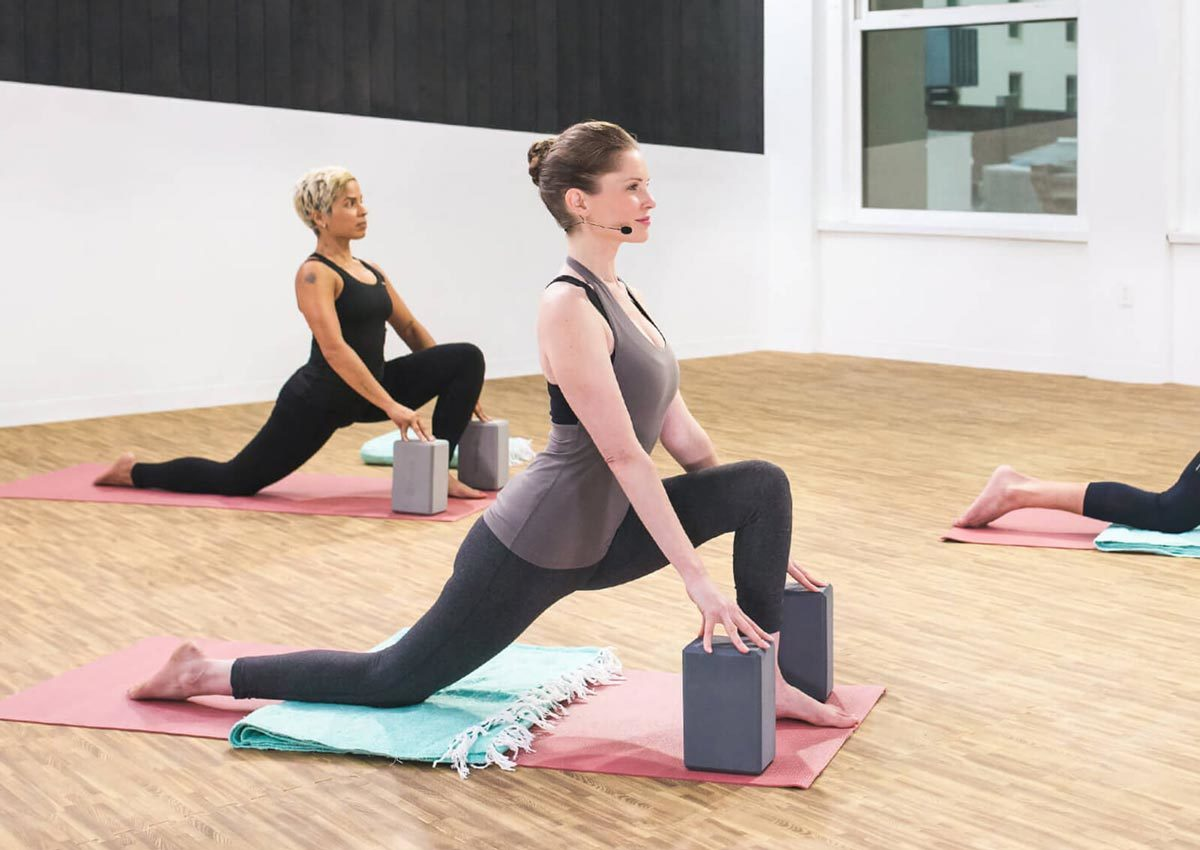 Daily Burn yoga instructor in a crescent lunge pose in the workout studio. photo