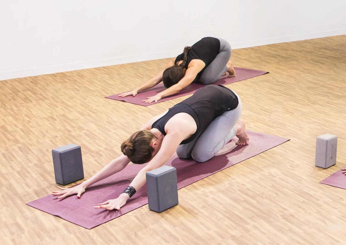 Daily Burn yoga instructor in child's pose with two blocks at the top of her yoga mat. photo