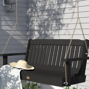 black hanging porch swing with a hat and blanket photo