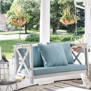white porch swing with blue cushion and pillows photo