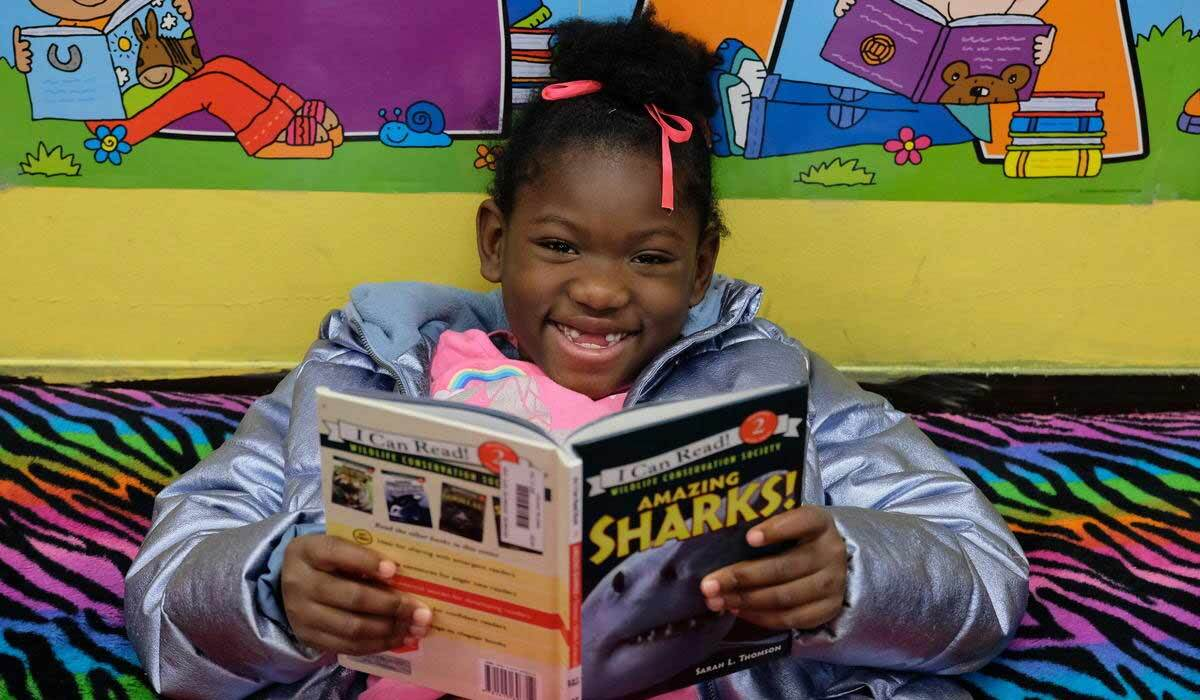 A girl smiles at the camera while reading a book photo