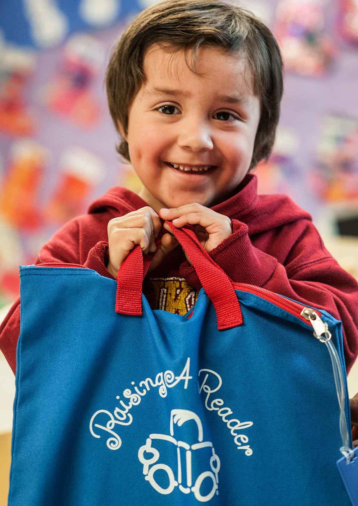 Young boy holding a school bag smiling at the camera photo