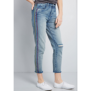 A woman wears medium blue boyfriend jeans with multicolored embroidered stripes down the side photo