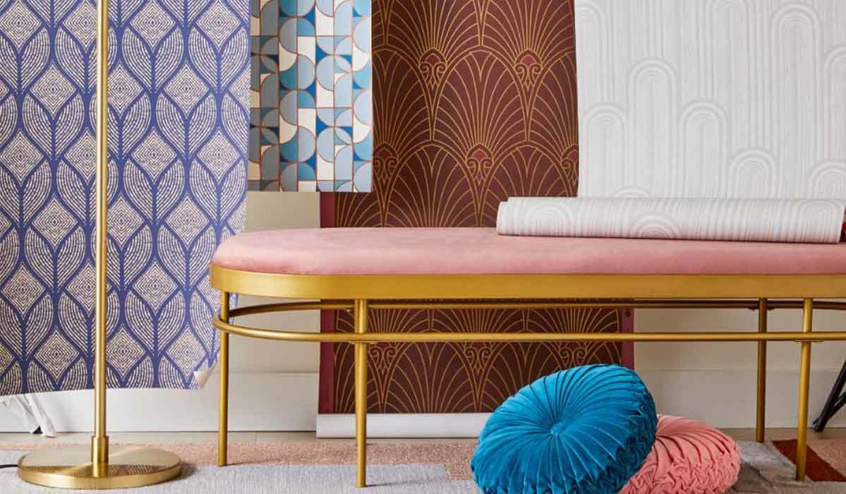 Pink and gold bench with blue and pink pillows on the floor photo