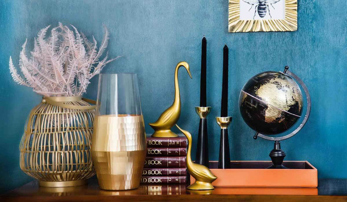 A shelf decorated with gold home decor