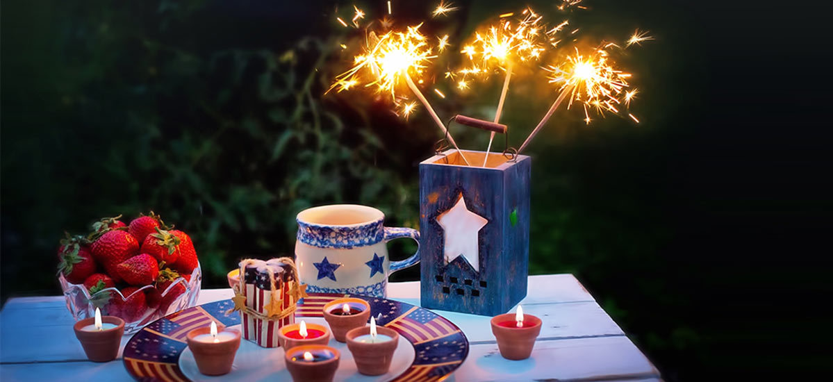 Outdoor picnic table with strawberries, candles, and sparklers on it.