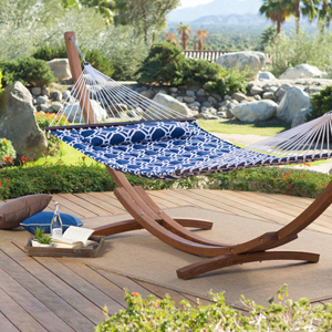 A patterned quilted hammock with a wooden stand on a backyard patio. photo