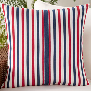 Red, white, and blue striped throw pillow on a white couch. photo