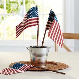 American flag in a tin bucket in the center of a dining table. photo