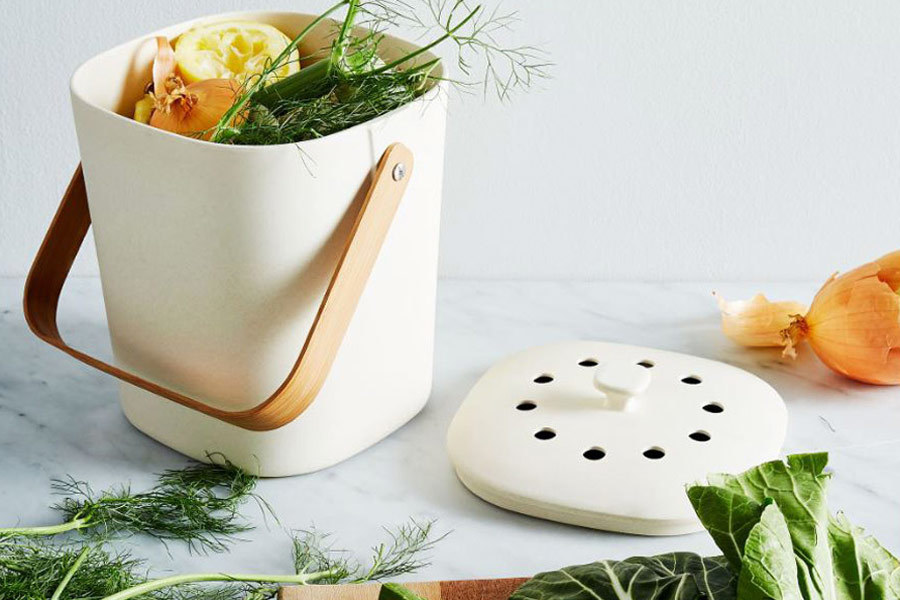 White bamboo compost bin with scraps inside photo
