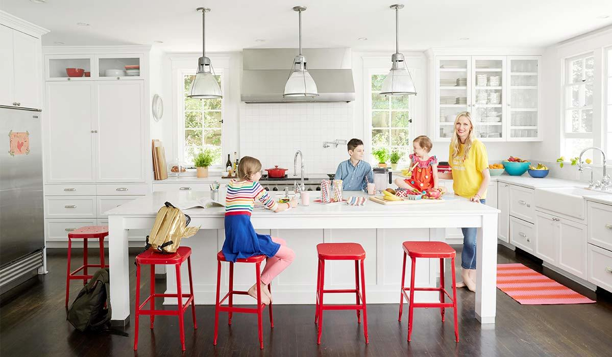 White kitchen with red stools, three kids, and a smiling woman photo