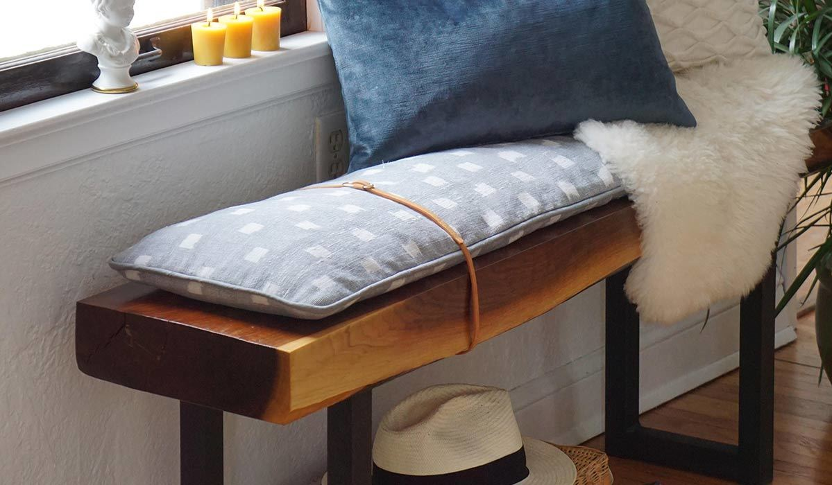 Bench with blue and white pillows and a fedora underneath it photo