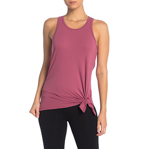 A woman wears a pink tank top with a tie at the side photo