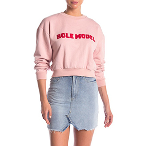 A woman wears a light pink Cynthia Rowley sweatshirt with the words
