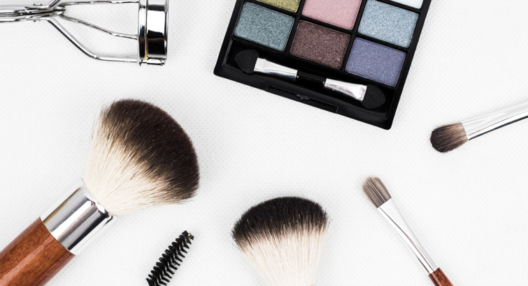 Spread of makeup including: eyeshadow, makeup brushes, and eyelash curler.
