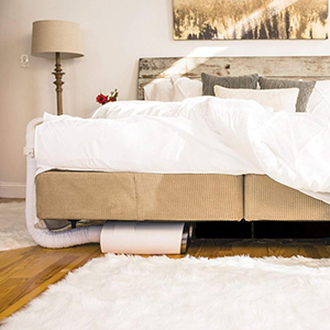 White and brown room with bedjet underneath bed photo