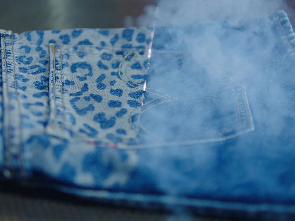 A close-up of a leopard pattern being designed onto a pair of Levi's denim shorts photo